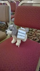 "A cuddly toy wolf with a sign reading ""werewolves are people too"" sits on a conference chair"