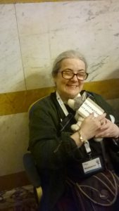 "A woman cuddles a cuddly toy wolf that has a sign reading ""werewolves are people too"""
