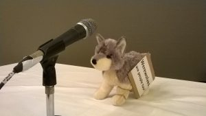 "A cuddly toy wolf with a sign reading ""werewolves are people too"" is at a microphone as though giving a speach"